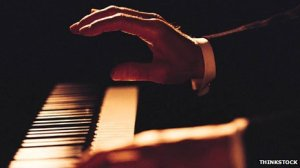 A musician's hand on a piano